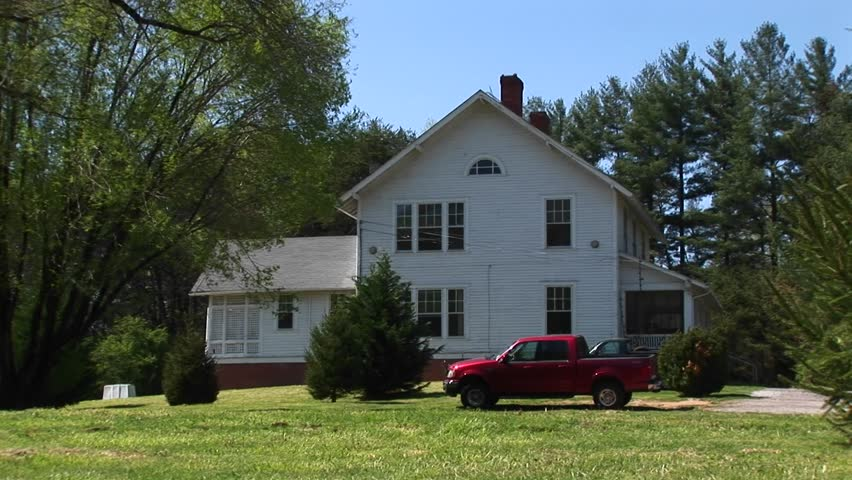 A newer model red pickup sits parked in front of a quaint white farmhouse.