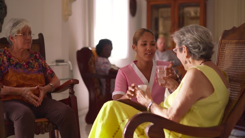 Old people in geriatric hospice: young attractive hispanic woman working as nurse helps a senior woman. She gives a water glass and prescription medicine to an elderly patient