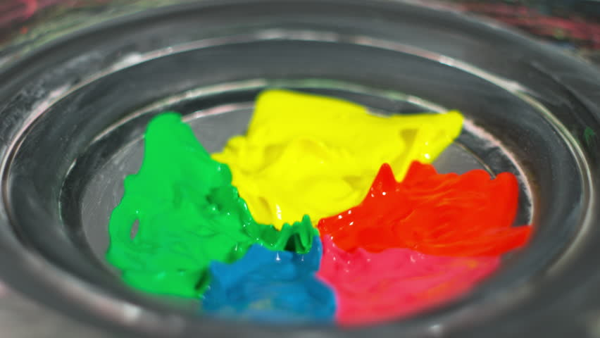 Rainbow blue, green, red, pink, and yellow paint bounces, splashing and mixing in creative artistic patterns on a thumping speaker playing loud music
