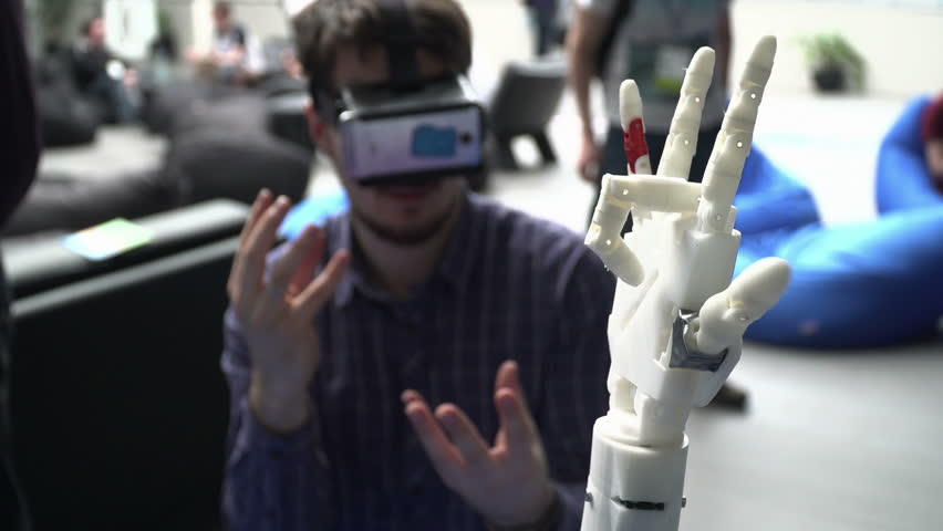 Cybernetic robot arm, which controls the people. Man controls robotic arm through virtual reality glasses. Playing the game or the game lives in another world. Hand as the Skynet | Shutterstock HD Video #15729073
