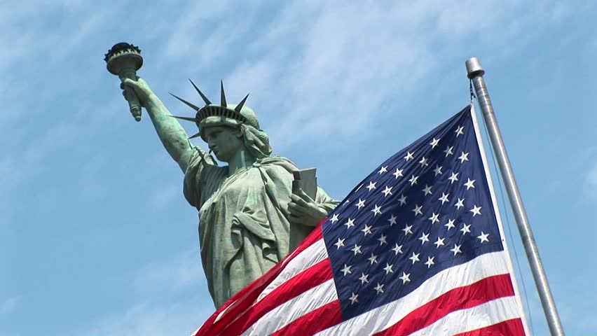 American flag waves in front of the Statue of Liberty circa 2006 in New York. | Shutterstock HD Video #1573171