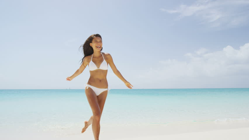 Beach bikini woman carefree running in freedom fun. Joyful happy Asian girl relaxing showing joy and happiness in slim body for weight loss diet concept on perfect white sand. Throwing beach hat.