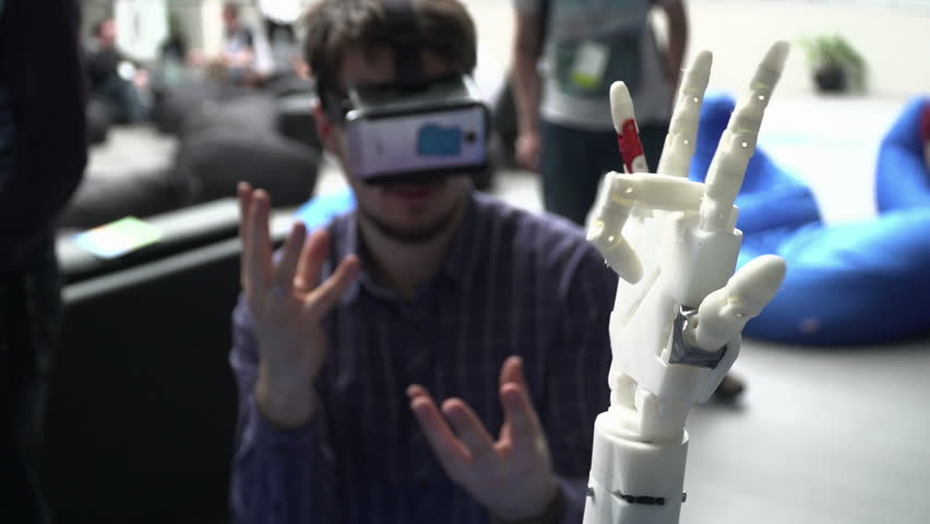 Ufa/Russia - 24 march 2016: Cybernetic robot arm, which controls people. Man controls robotic arm through virtual reality glasses. Playing game or the game lives in another world. Hand as the Skynet | Shutterstock HD Video #15787348