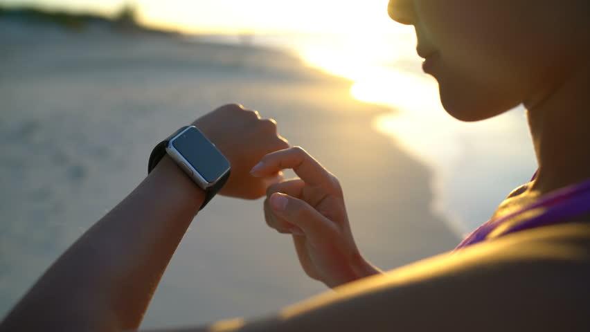 Smartwatch. Young woman using smart watch on beach. Closeup of female touching touch screen on watch entering watch app. | Shutterstock HD Video #15796489