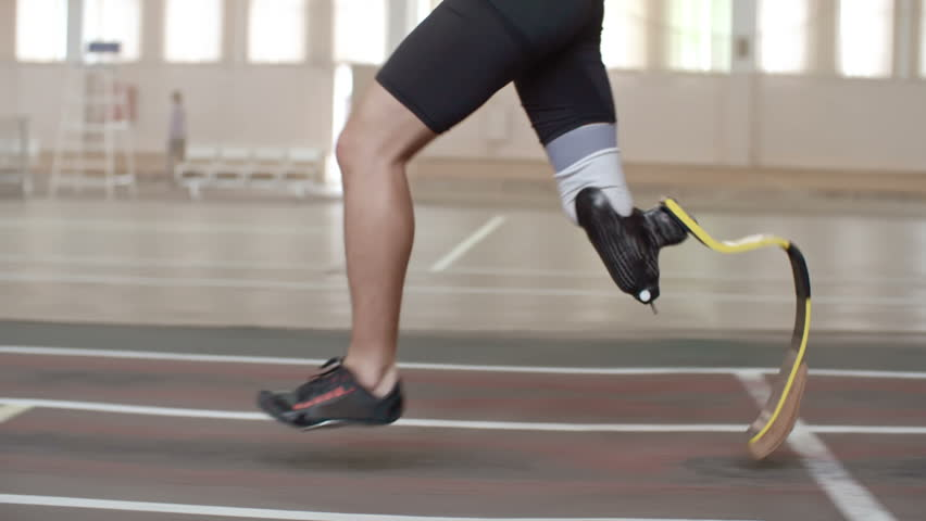 Tracking shot tilt-up of determined Paralympic athlete with prosthetic leg running on track in slow motion