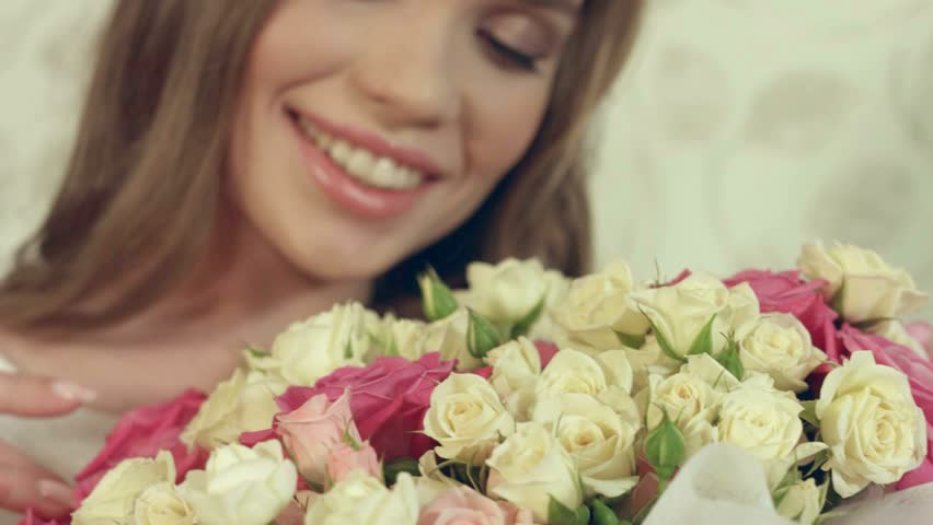 Portrait of beautiful girl posing with a big bouquet of delicate roses #15809833