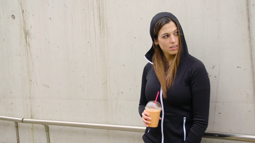 Sporty woman resting after urban fitness workout for drinking detox orange smoothie. Tired female athlete taking a training break leaning on a city wall.    Shutterstock HD Video #15813289