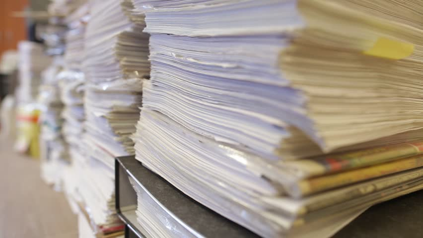 Piles of documents stored in the office. Bureaucracy and paperwork concept. Dolly shot and close up on the objects.
