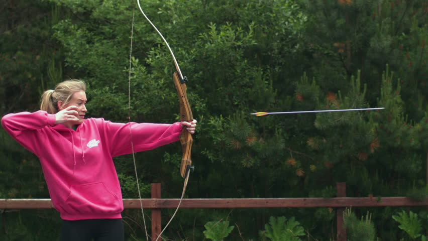 Blonde woman shooting bow and arrow in cinemagraph style