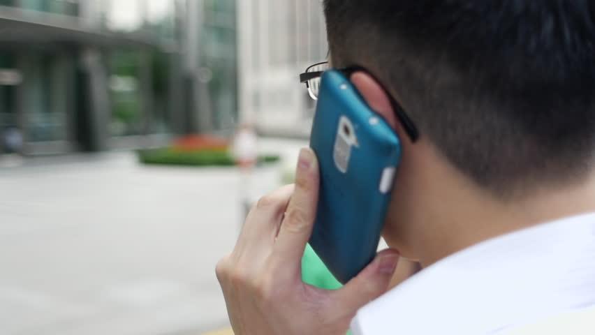Asianman on the phone walking