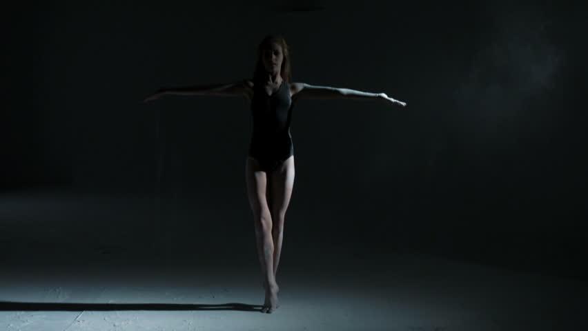 Caucasian teenager dancer black leotard indoors studio freestyle dancing powder spot light dramatic edgy movement interpretation
