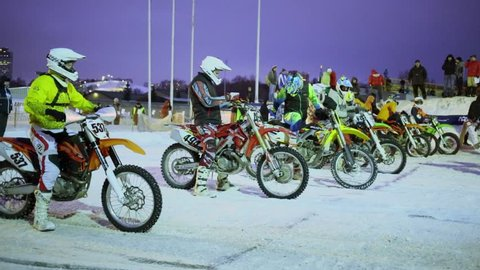 MOSCOW - FEB 14, 2015: Row of riders stand on start line on motordrome in Krylatskoe at winter evening