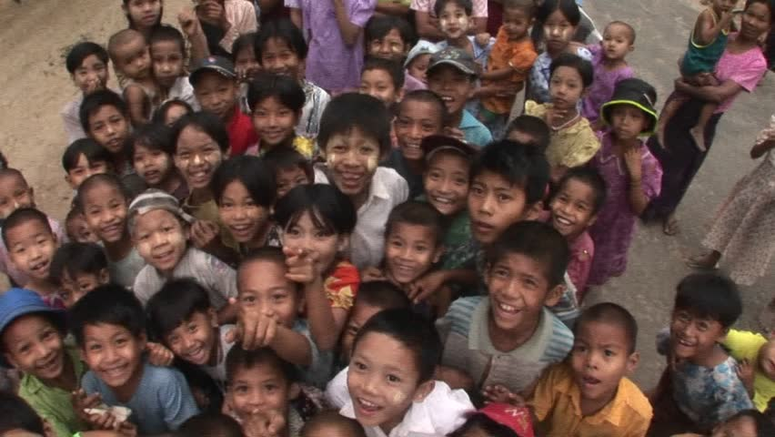 MYANMAR - CIRCA 2009: A crowd of children smile and wave at the camera circa 2009 in Myanmar.