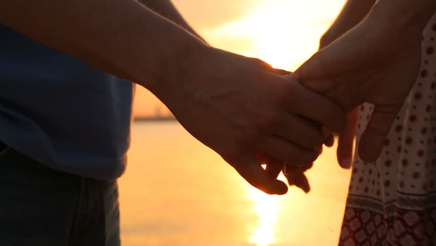 man and woman holding hands at sunset. close-up of hands #15868867