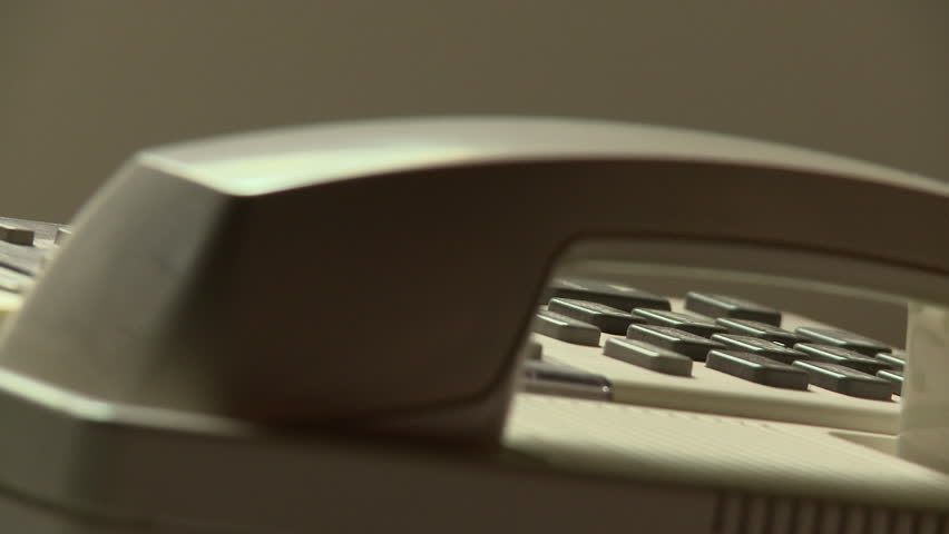 A man picks up the receiver and pushes the buttons on a 1980s era telephone. He dials 911. He returns the handset to the phone base.