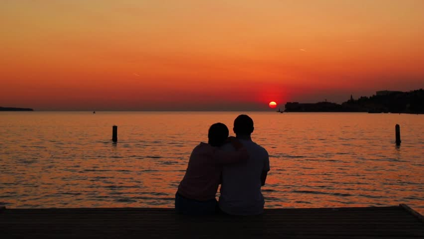 Romantic family scene: silhouette of couple at the sea background. Family couple sitting on the beach. The couple looks at the sunset on the Adriatic sea. A pair of lovers watching the sunset. Piran