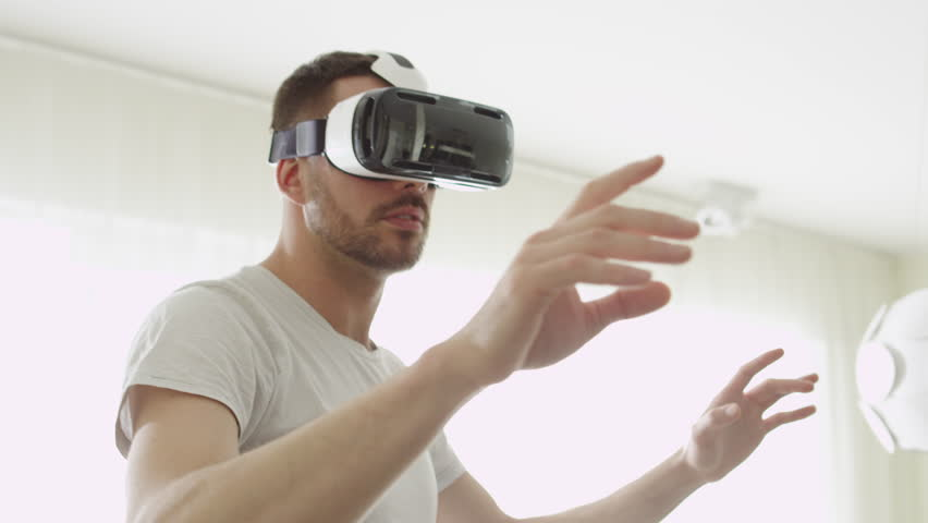 Man Wearing VR Headset at Living Room. Using Gestures with Hands. Shot on RED Cinema Camera. | Shutterstock HD Video #15906697