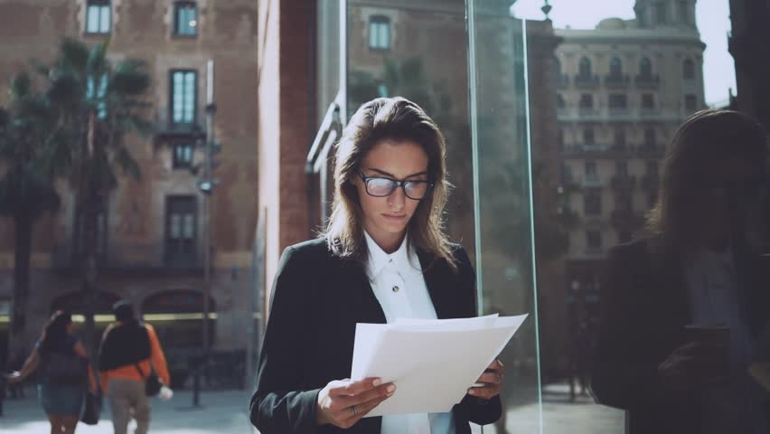 Young professional businesswoman or female manager looking concentrated on documents, outdoors   Shutterstock HD Video #15911686