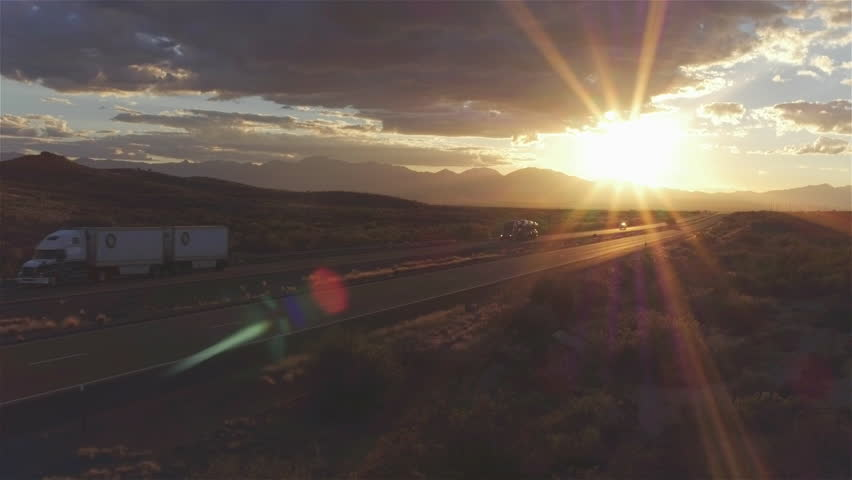 4K AERIAL: Cars and freight semi truck driving on busy highway across the country in beautiful summer evening. People on road trip traveling on busy freeway at golden sunset | Shutterstock HD Video #15953443