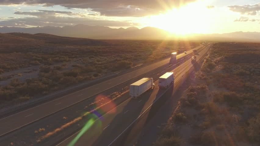 4K AERIAL: Cars and freight semi truck driving on busy highway across the country in beautiful summer evening. People on road trip traveling on busy freeway at golden sunset   Shutterstock HD Video #15953464