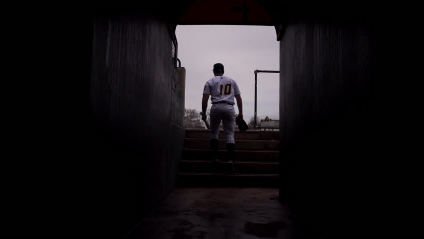 Slow motion wide shot of baseball player walking to field in tunnel