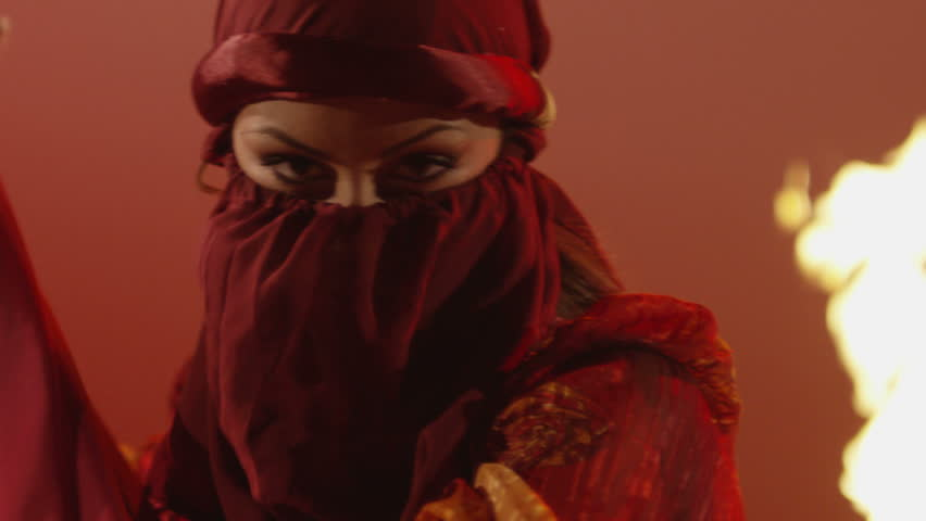 Beautiful traditional oriental belly dancer. Oriental girl dancing on red background. Studio shoot with fire.  Shot on RED EPIC DRAGON Cinema Camera in slow motion. #15955936