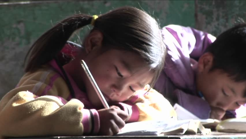 BEIJING, CHINA - CIRCA 2009: Children practice writing in a rural classroom circa 2009 in Beijing.