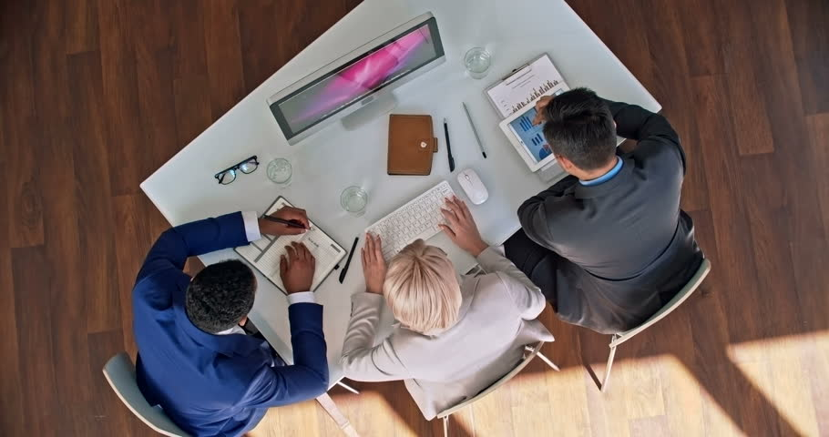 Directly above view of two businessmen and businesswoman working together at the desk: one of them writing in his note pad, woman typing on a computer keyboard and another man using digital tablet | Shutterstock HD Video #15960217