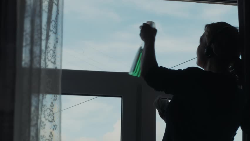The woman washes a window and listening to music on headphones . Spring mood. Bringing order . Cleaning service . Good hostess.  | Shutterstock HD Video #15968161