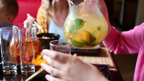 Girl in pink pouring lemonade from carafe into glass at table in sushi restaurant.