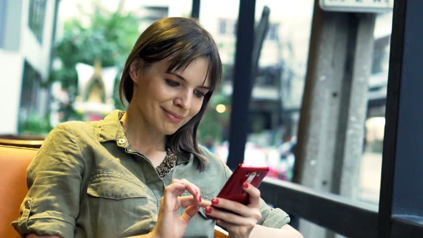 Young, pretty woman using smartphone in cafe in city    Shutterstock HD Video #15987565