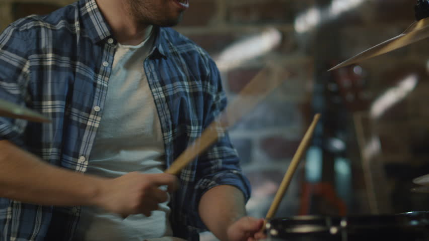 Drummer plays music while rehearsing a song in a home studio in a garage. Shot on RED Cinema Camera in 4K (UHD).
