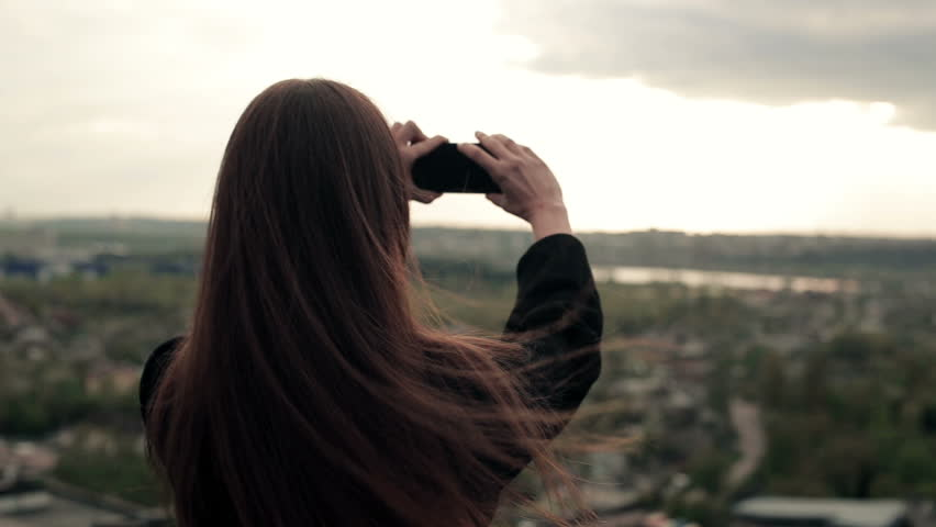 Young woman uses a smartphone on the roof   Shutterstock HD Video #16005667