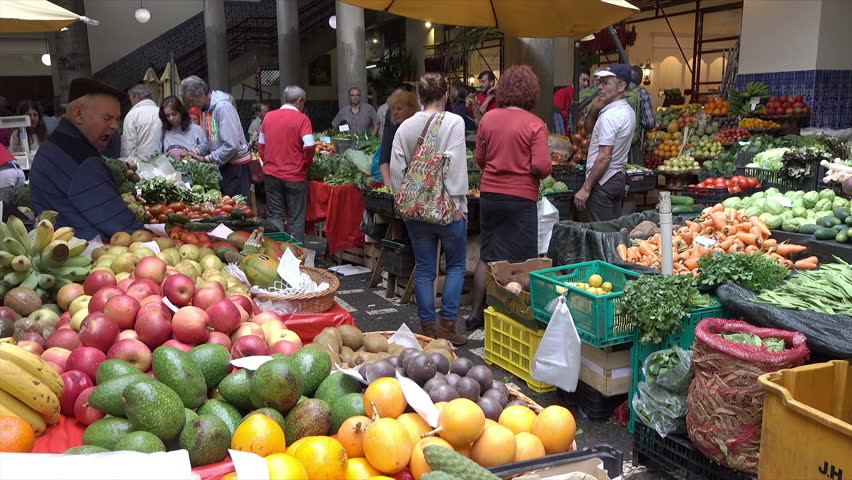 FUNCHAL, MADEIRA/PORTUGAL - JANUARY 23, 2016: Unidentified people shop at fruit stall at Workers Market. The worker's market was built in 1940 to provide a central location to sell local produce.