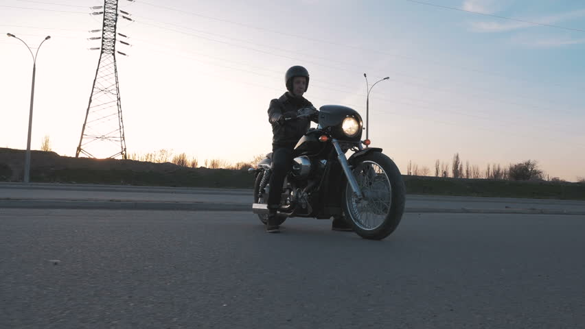 Young man sitting on motorcycle on the road at sunset, slow motion | Shutterstock HD Video #16016023