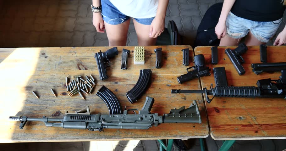table full of firearms arsenal cute girl reloading gun. Pan across a variety of handheld firearms, shotguns, rifles, semi automatic guns ammunition clip spinning Action movie essential, Ak47 millitia