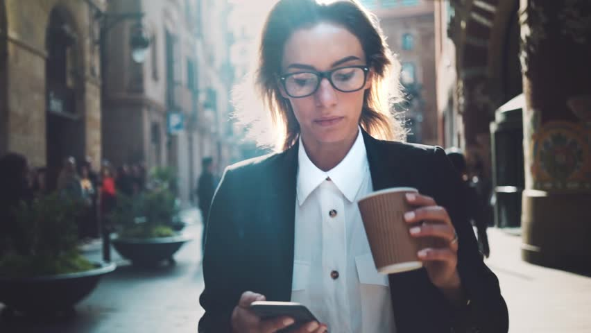 Young professional businesswoman walking on city streets and drinking coffee to go, sunshine, slow motion | Shutterstock HD Video #16045831