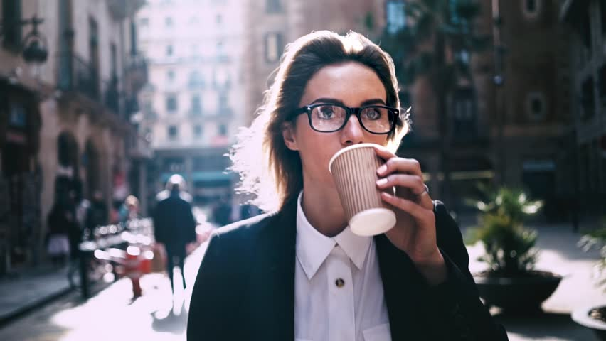 Portrait of young attractive businesswoman drinking coffee to go on a break and using modern smartphone outdoors, sunshine, slow motion   Shutterstock HD Video #16045861