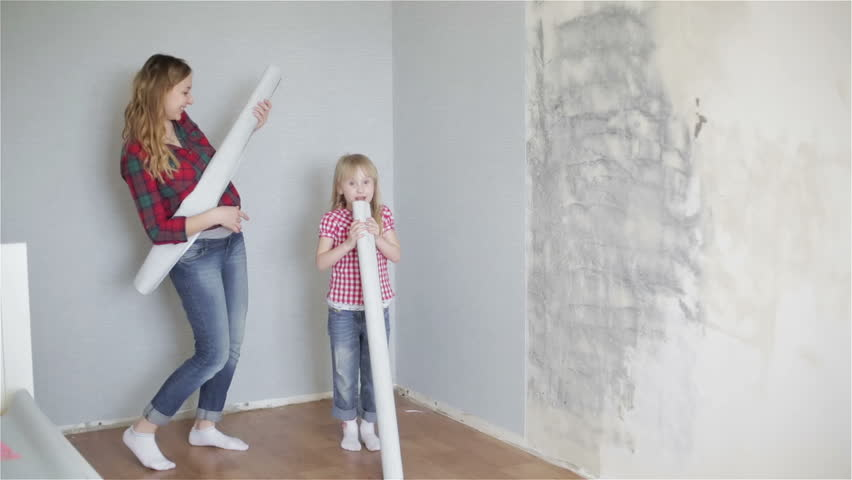 Cheerful girls are dancing and singing near the wall with rolls of wallpaper in their hands. Happy funny family is fooling around. Pregnant woman and her daughter are doing repair in the room. #16048357