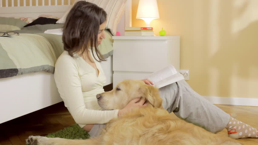 A girl reading book with her dog at home | Shutterstock HD Video #16052617
