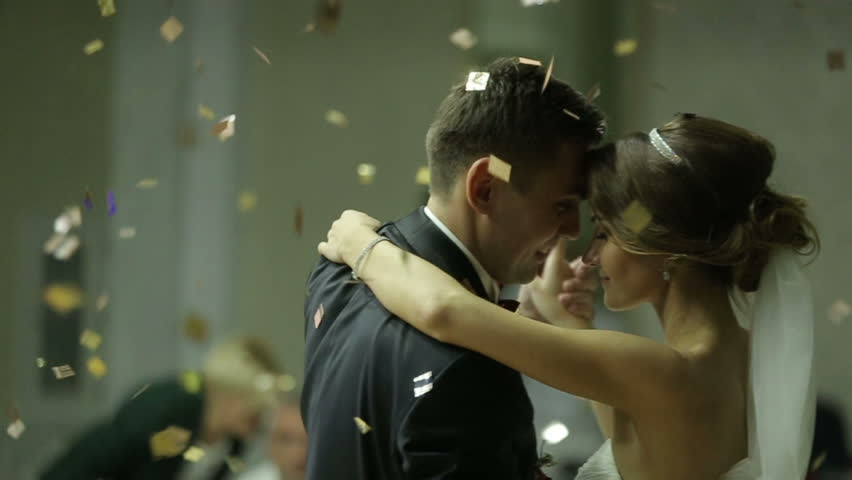 Beautiful brunette bride and handsome groom dancing first dance at the wedding party. Confetti in the air. Very tender moment | Shutterstock HD Video #16053757