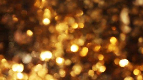 Golden glitter bokeh lights, Out of focus background, slow motion