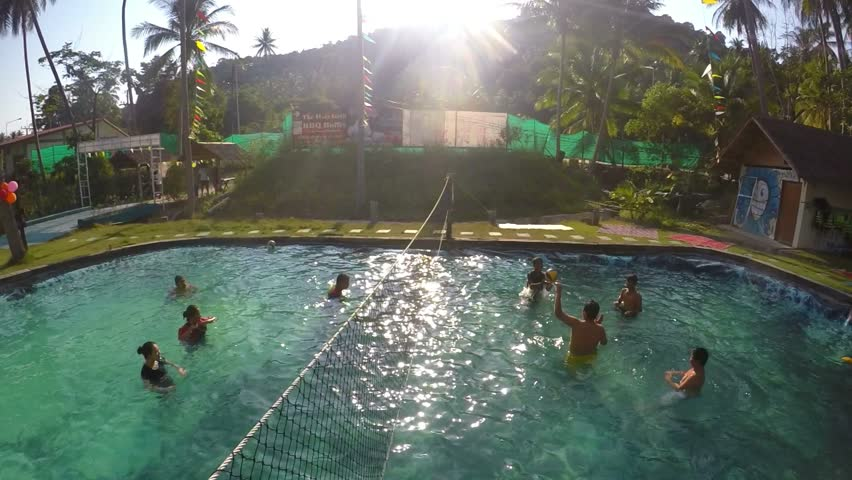 THAILAND, KOH SAMUI, 13.04.2016 - Group of People Playing Volleyball in Pool at Sunset. Slow Motion.