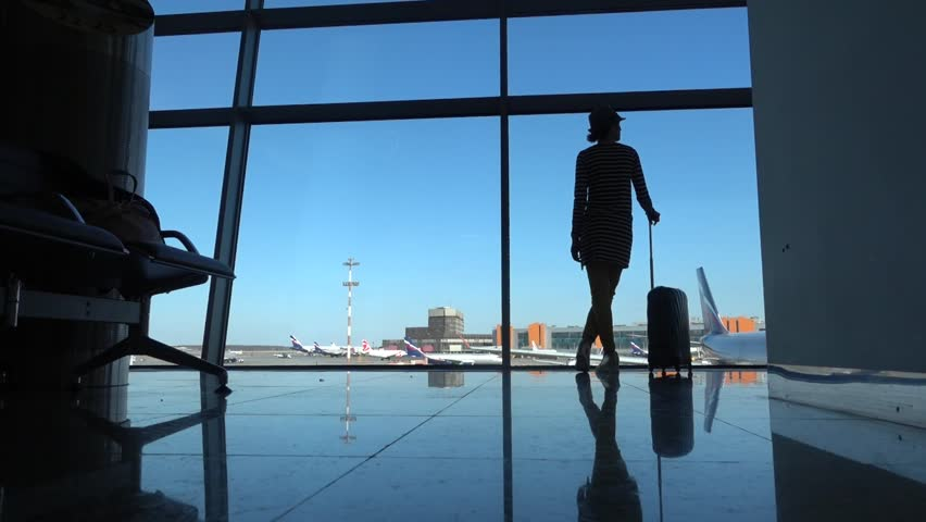 Female walking through the airport using her smartphone device. | Shutterstock HD Video #16087702