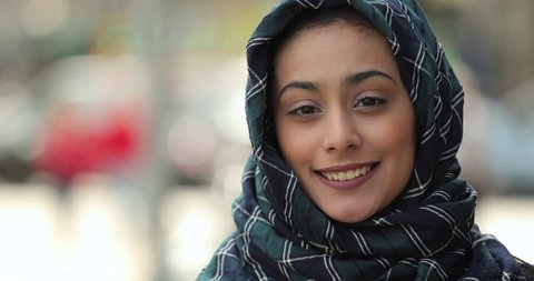 Young woman wearing hijab in city serious to smile face portrait