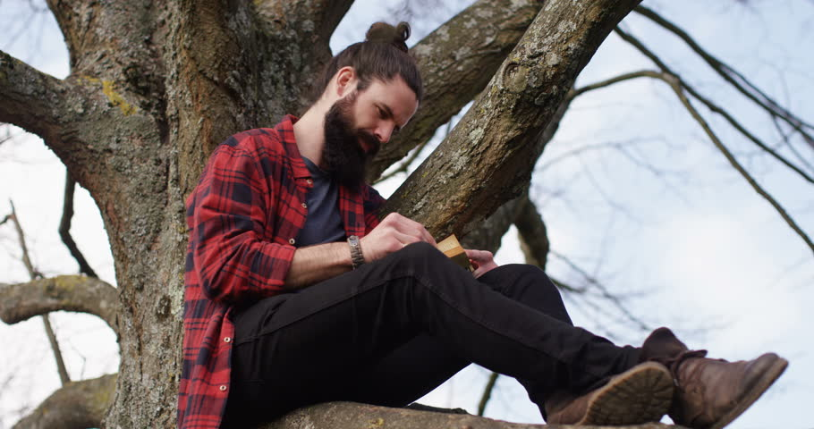 4k young carefree man sitting on a tree trunk away from hustle and bustle of a city and reading a book. | Shutterstock HD Video #16143127