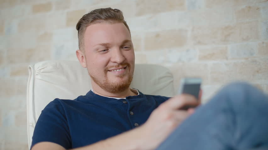 The young man smiles and corresponds with someone by phone. The man has decided to have a rest at Friday evening and brings together the company.