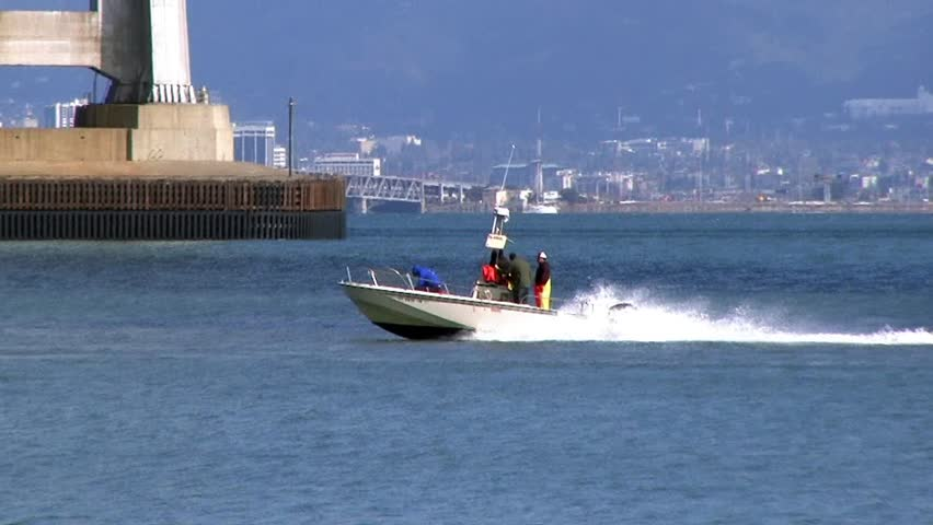 Motor boat going under bay bridge, San Francisco Bay