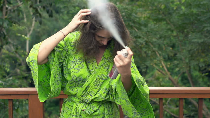 Woman in bathrobe applying hairspray on hair on terrace, super slow motion 240fps