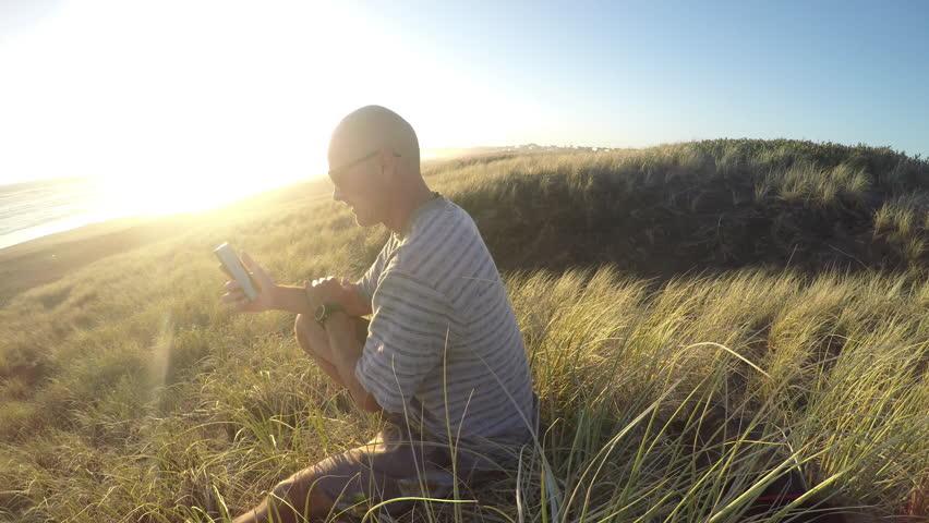 Man sitting in sand dunes at beach using smart phone  | Shutterstock HD Video #16167310